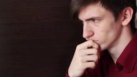 一件红色衬衣的一个年轻人接触他的有他的下巴的手,仔细地看 股票录像