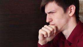 一件红色衬衣的一个年轻人,标榜他的面孔,盖他的嘴唇用他的手指 股票视频