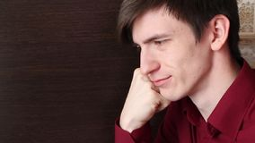 一件红色衬衣的一个年轻人,紧张,扶植他的下巴用拳头 影视素材