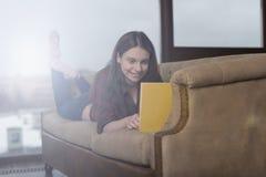 一件红色衬衣的女孩在长沙发 免版税库存图片