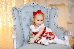 一件红色褂子的小女婴迷人的金发碧眼的女人摆在一张面孔,坐 库存图片