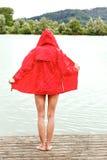 一件红色雨夹克的愉快的妇女 免版税库存照片