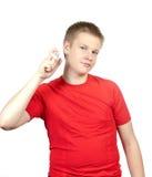 一件红色T恤杉的少年有一个瓶的香露在手上 免版税库存图片