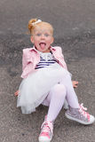 一件美丽的使用的礼服和的运动鞋的一个逗人喜爱的小女孩  免版税库存照片