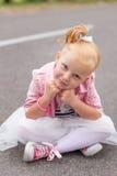 一件美丽的使用的礼服和的运动鞋的一个逗人喜爱的小女孩  图库摄影