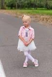 一件美丽的使用的礼服和的运动鞋的一个逗人喜爱的小女孩  库存图片