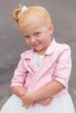 一件美丽的使用的礼服和的运动鞋的一个逗人喜爱的小女孩  免版税图库摄影