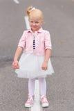 一件美丽的使用的礼服和的运动鞋的一个逗人喜爱的小女孩  免版税库存图片