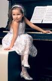 一件美丽的礼服的女孩坐在钢琴 免版税库存照片