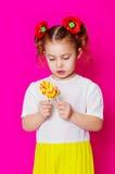 一件美丽的礼服的小女孩有一个大糖果棒棒糖的 库存图片