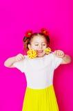 一件美丽的礼服的小女孩有一个大糖果棒棒糖的 图库摄影