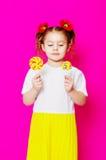一件美丽的礼服的小女孩有一个大糖果棒棒糖的 库存照片
