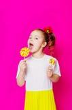 一件美丽的礼服的小女孩有一个大糖果棒棒糖的 免版税库存照片