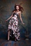 一件美丽的礼服的年轻红头发人女孩 图库摄影