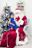 一件美丽的蓝色礼服的小女孩坐膝部在圣徒尼古拉斯 免版税库存照片
