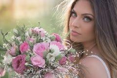 一件美丽的豪华的礼服的美丽的时髦的新娘在拿着新娘花束的森林里 免版税库存图片