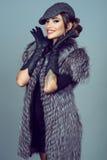一件美丽的迷人的微笑的模型佩带的银狐夹克的画象 免版税库存图片