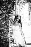 一件美好的婚礼长的礼服的新娘,棕榈树背景的年轻性感的妇女  免版税库存照片