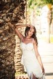一件美好的婚礼长的礼服的新娘,棕榈树背景的年轻性感的妇女  免版税图库摄影