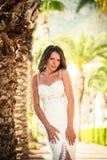 一件美好的婚礼长的礼服的新娘,棕榈树背景的年轻性感的妇女  免版税库存图片