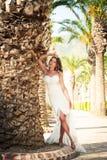 一件美好的婚礼长的礼服的新娘,棕榈树背景的年轻性感的妇女  库存图片