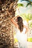 一件美好的婚礼长的礼服的新娘,棕榈树背景的年轻性感的妇女  库存照片