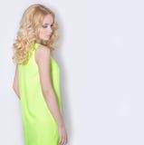 一件黄色夏天礼服的美丽的性感的白肤金发的女孩有头发的卷曲 免版税库存图片