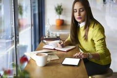 一件黄色女衬衫的美丽的浅黑肤色的男人在网上数据库中检查会计的通过触感衰减器与屏幕的嘲笑连接了到wifi 免版税库存照片