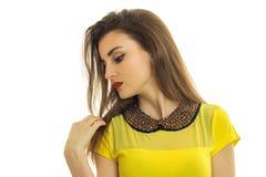 一件黄色女衬衫的迷人的女孩竖起了她的头对边和神色下来特写镜头 库存照片