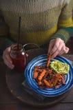 一件绿色毛线衣的妇女吃油煎的红萝卜拷贝空间的 库存照片