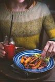 一件绿色毛线衣的妇女吃油煎的红萝卜的 免版税库存照片