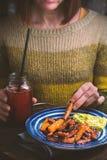 一件绿色毛线衣的妇女吃从板材的油煎的红萝卜 免版税库存照片