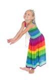 一件色的礼服的嬉戏的女孩 免版税库存图片