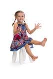 一件色的礼服的小女孩在椅子 免版税库存照片