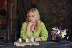 一件绿色礼服的北欧海盗白肤金发的女孩坐在一张木桌上 免版税库存图片