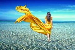 一件黄色礼服的女孩在海 免版税图库摄影