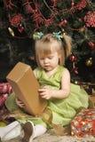 一件绿色礼服的小女孩在圣诞树下 免版税库存图片