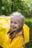 一件黄色礼服的微笑的女孩有一把伞的在一个多雨春天晴天 免版税库存图片