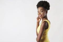 一件黄色礼服的微笑的女孩 免版税库存图片