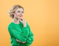 一件绿色礼服的白肤金发的女孩在黄色背景 妇女在面孔附近握一只手并且看照相机 库存图片