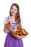 一件紫色礼服的白肤金发的妇女有椒盐脆饼篮子的  免版税库存图片