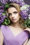 一件紫色礼服的美丽的女孩和丁香花束  模型在春天的图象 库存照片