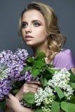 一件紫色礼服的美丽的女孩和丁香花束  模型在春天的图象 免版税库存图片