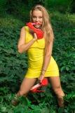 一件黄色礼服的美丽的运动女孩有红色鞋子的在手中 免版税库存照片