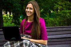 一件紫色礼服的迷人的女孩坐一条长凳在公园w 免版税库存照片