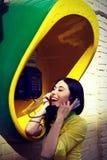 一件黄色衬衣的女孩在电话箱子 库存图片