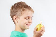 一件绿色衬衣的小男孩用水多的黄色梨 免版税库存照片