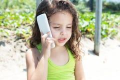 一件黄色衬衣的幼儿讲话在电话 免版税库存照片