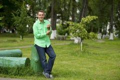 一件绿色衬衣的年轻英俊的人在夏天背景  图库摄影