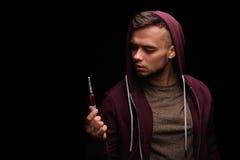 一件紫色运动衫的一个上瘾的吸毒者遭受与一个注射器的毒瘾在黑背景的一只手上 库存图片
